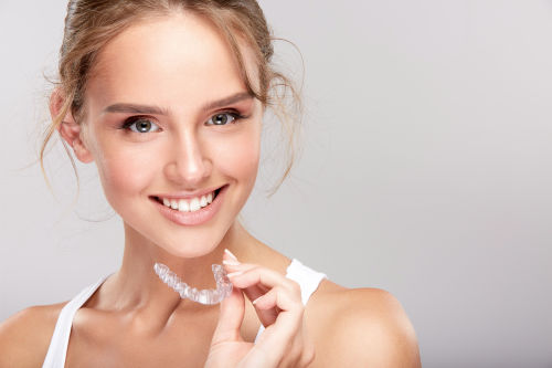 Woman holding Invisalign aligner in Wellesley and Weston, MA.